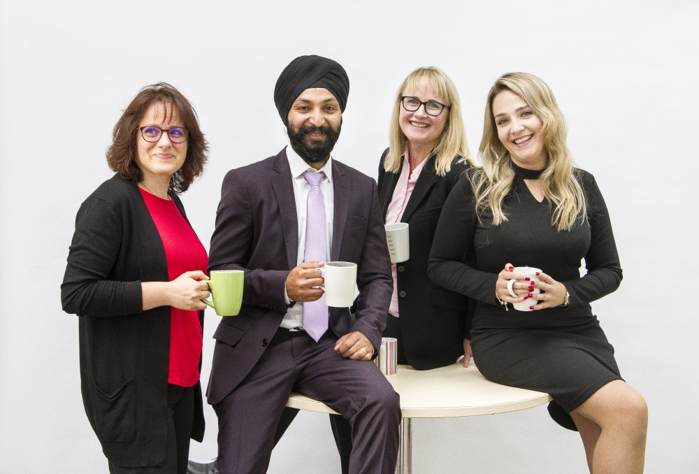 Photo of 4 members of staff withmsiling with coffee cups